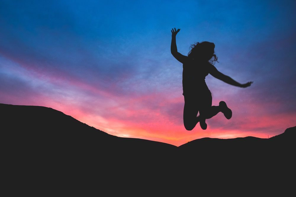 Silhouette of woman jumping to celebrate