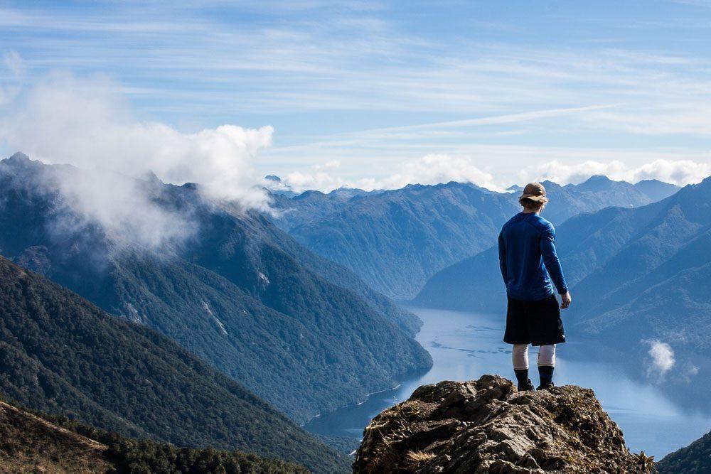 Man on ridge overlooking lakes and mountains